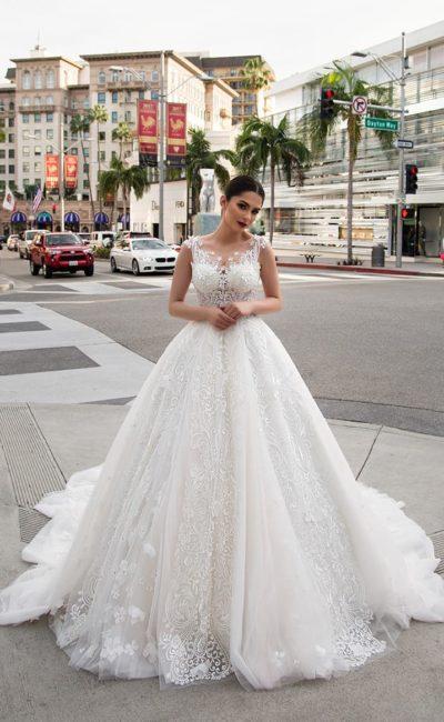 Эффектное свадебное платье с крупной ажурной отделкой и пышной юбкой сложного кроя.
