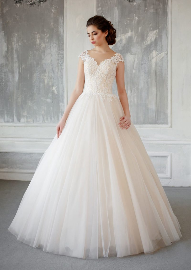 Деликатное свадебное платье оттенка слоновой кости с коротким рукавом и пышной юбкой.