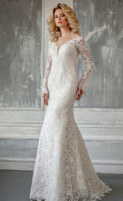 Эффектное свадебное платье с кружевной отделкой, вырезом и длинным рукавом.