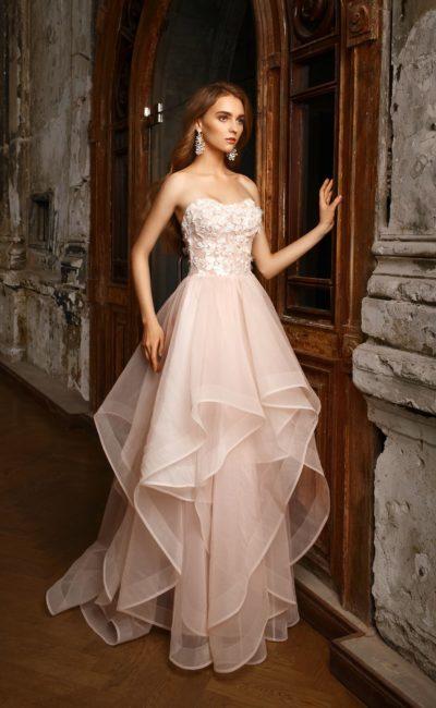 Открытое свадебное платье с объемной отделкой корсета и многослойным пышным подолом.
