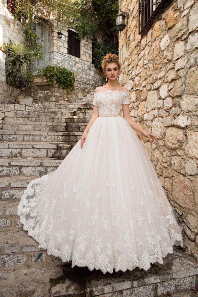 Кружевное свадебное платье пышного кроя с элегантным портретным декольте и поясом.