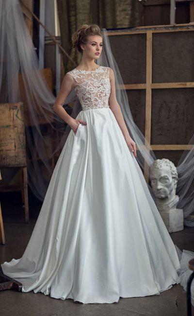 Атласное свадебное платье со скрытыми карманами и полупрозрачным закрытым верхом.