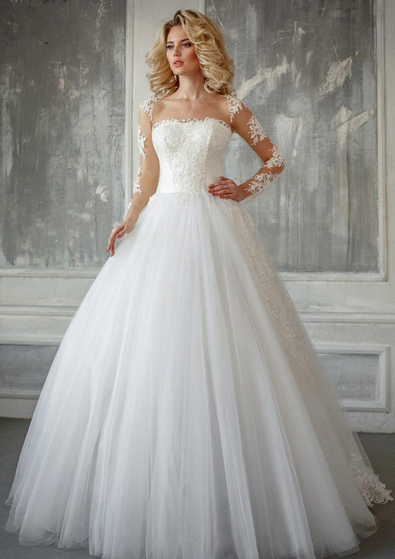 Пышное свадебное платье с длинным прозрачным рукавом, украшенным аппликациями.