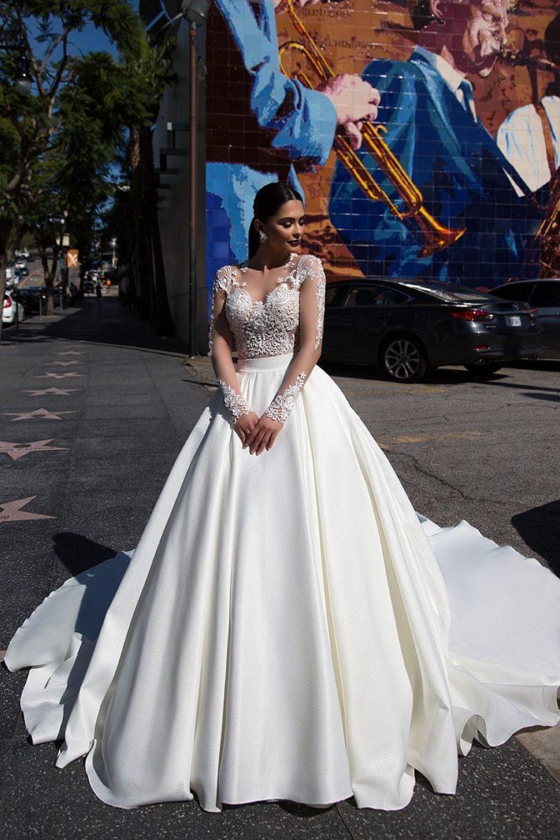Утонченное свадебное платье с кружевным верхом и пышной юбкой из атласной ткани.