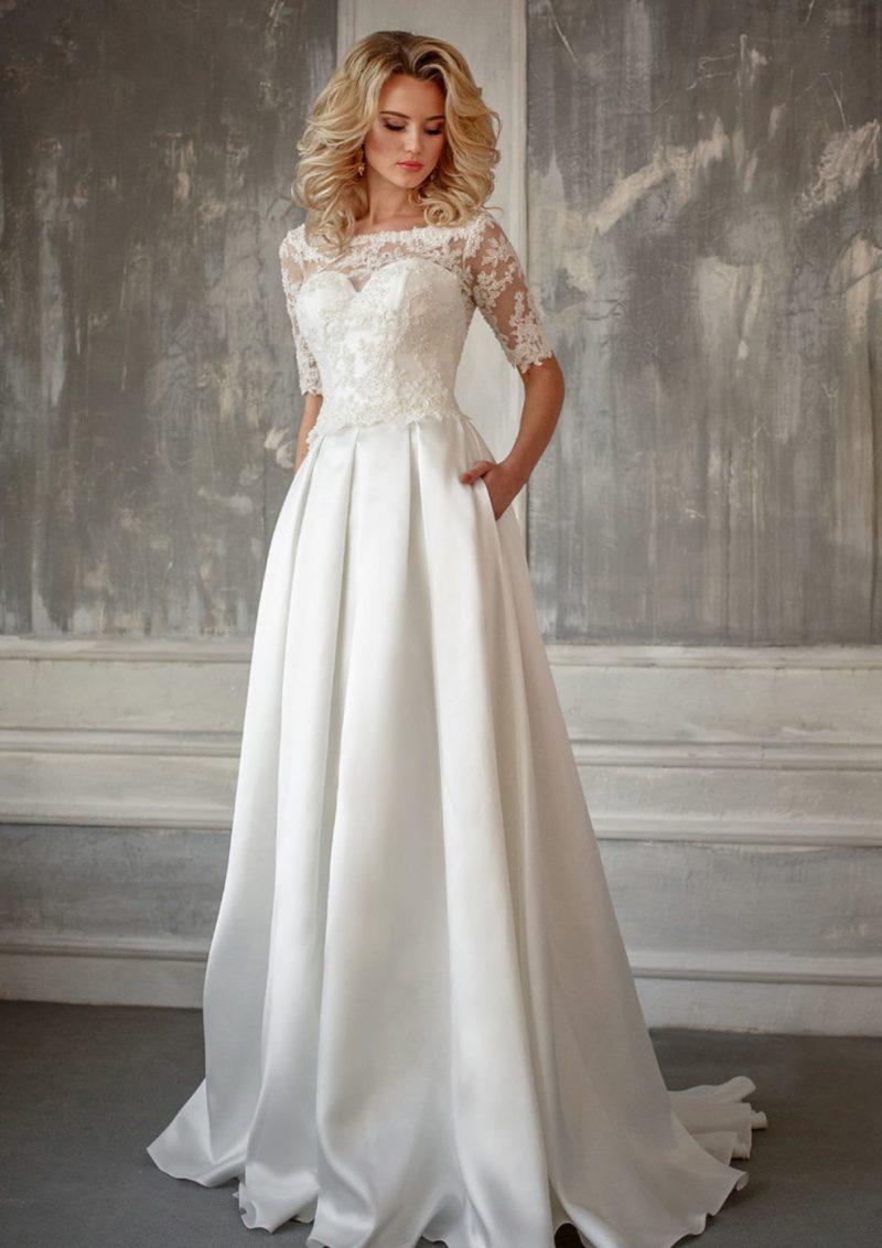 Закрытое свадебное платье с атласной юбкой «принцесса» со скрытыми карманами.