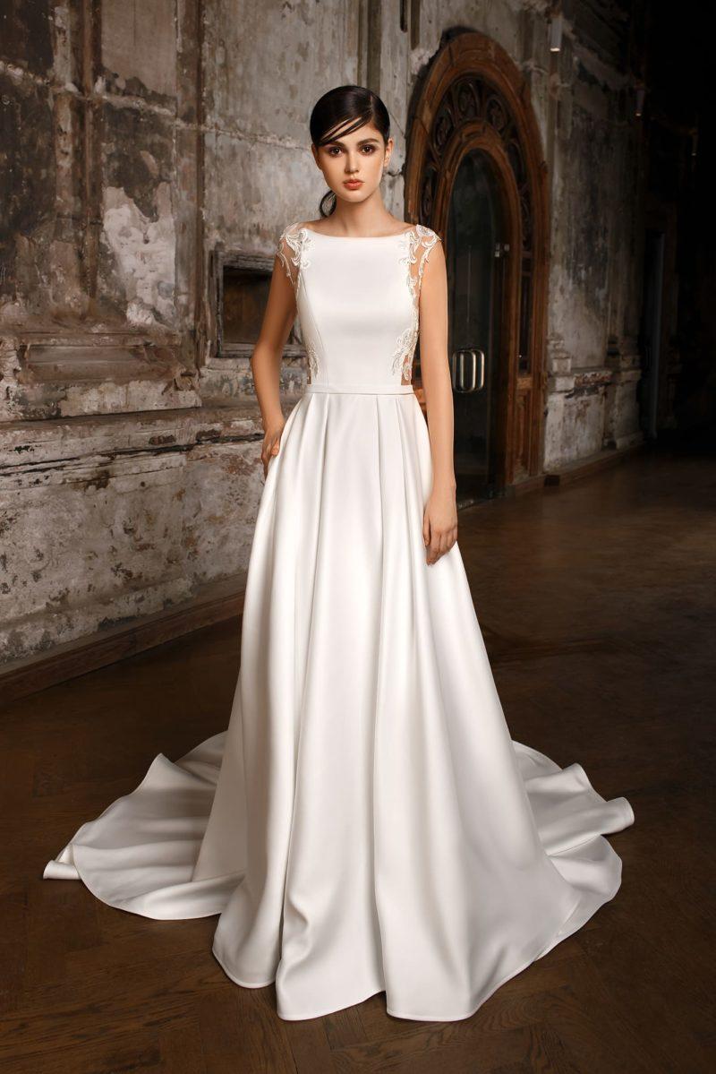 Атласное свадебное платье с вырезом под горло, полупрозрачной спинкой и длинным шлейфом.