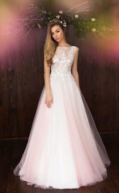 Закрытое свадебное платье кремового оттенка с многослойной юбкой и кружевом на лифе.