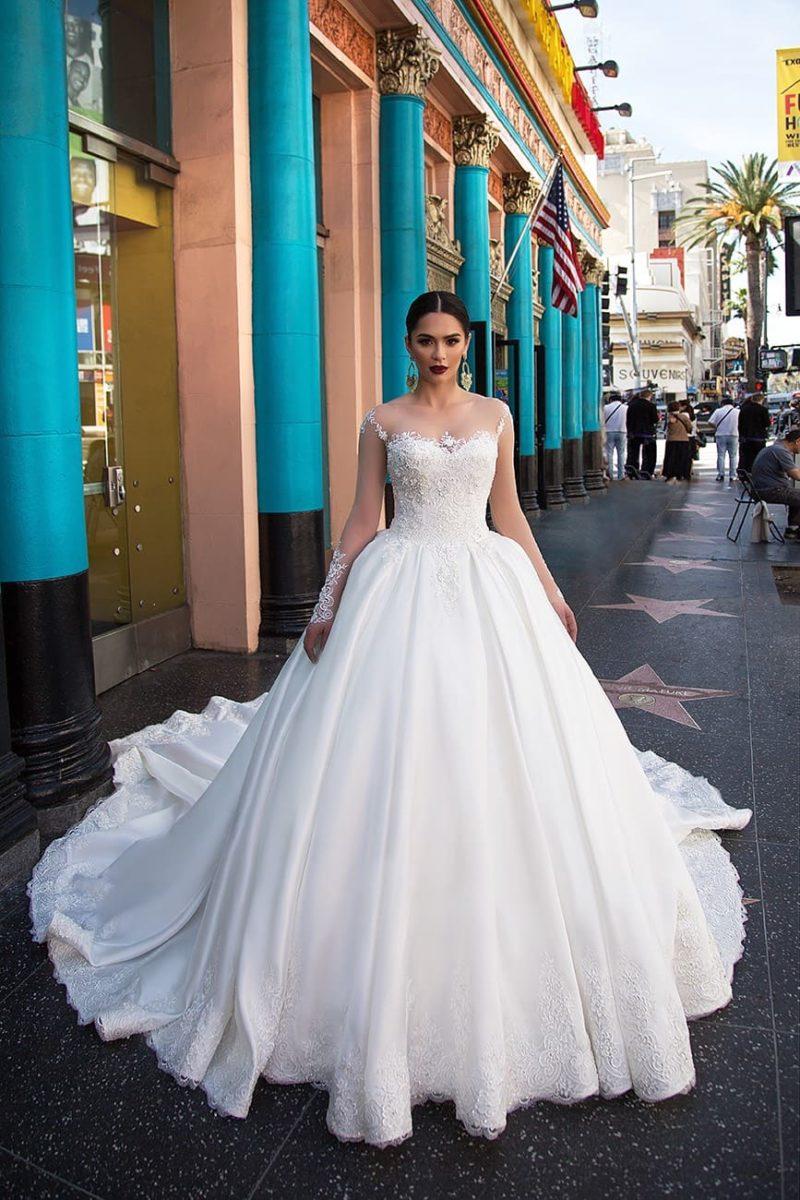 Пышное свадебное платье с узкими бретелями, кружевным декором и атласной юбкой.