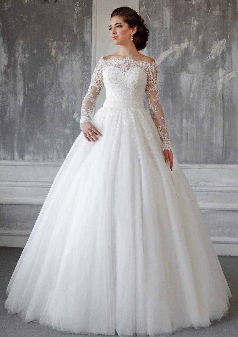 Пышное свадебное платье с фигурным кружевным декольте и утонченными рукавами.