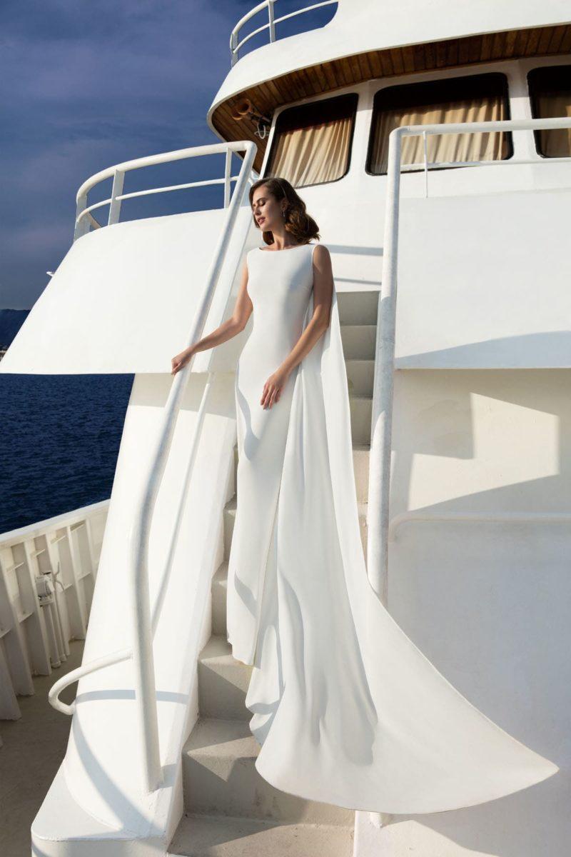 Утонченное свадебное платье прямого кроя с закрытым лифом и стильным кейпом на плечах.