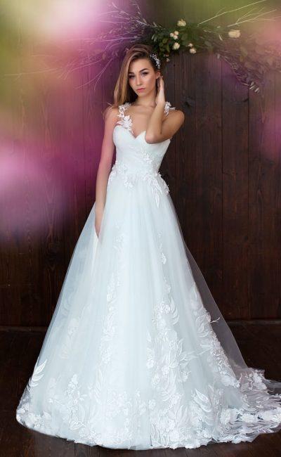 Свадебное платье с асимметричным лифом и многослойной юбкой А-силуэта со шлейфом.