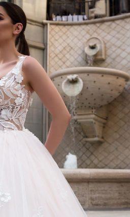 Пудровое свадебное платье с романтичной отделкой по низу пышной юбки и открытым верхом.