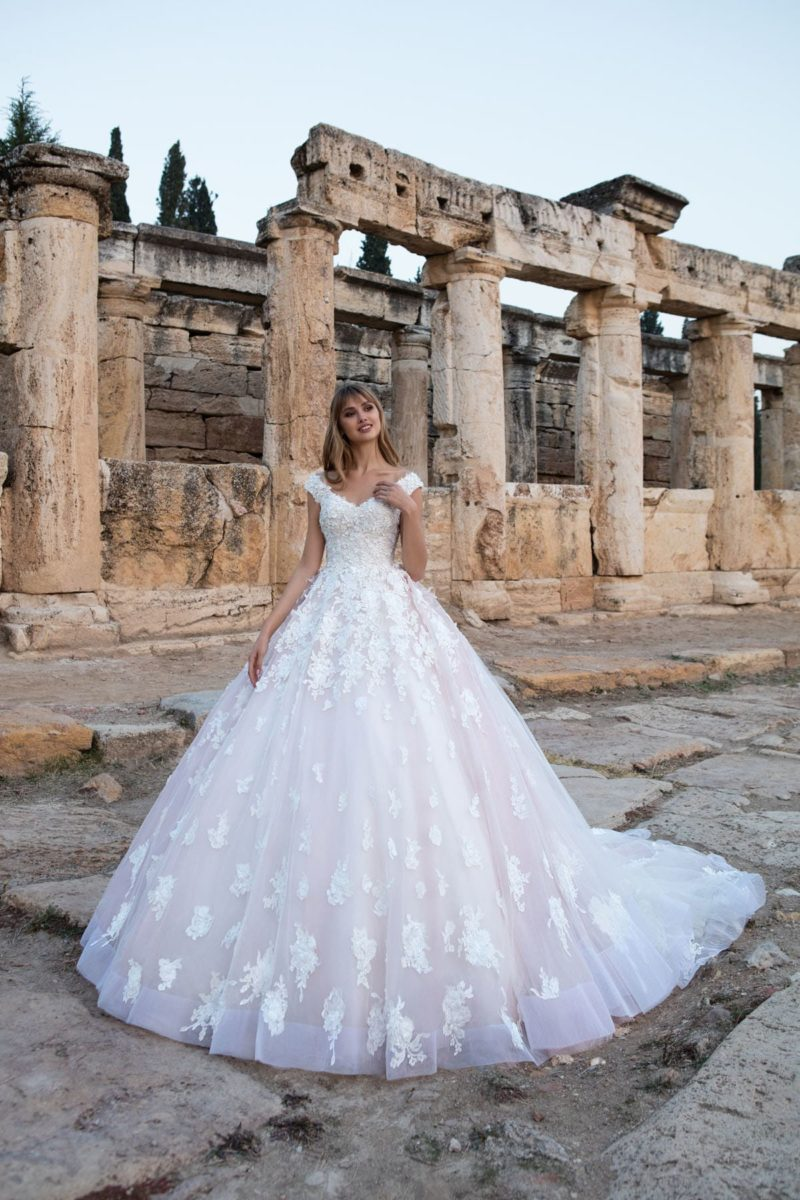 Подчеркнуто пышное свадебное платье с бежевой подкладкой юбки, шлейфом и белым кружевом.