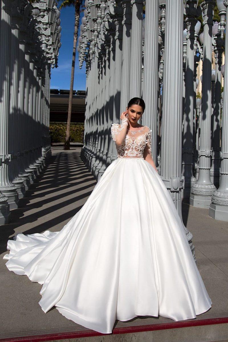 Свадебное платье с пышной атласной юбкой и соблазнительным полупрозрачным верхом.