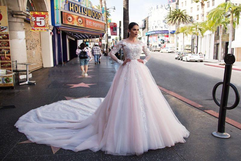 Пышное свадебное платье пастельного розового оттенка с длинным рукавом и кружевом.