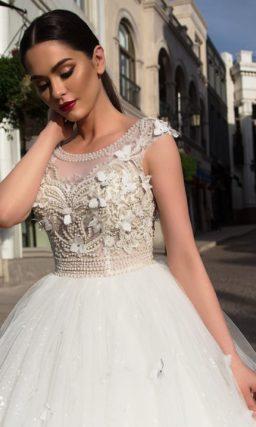 Фантазийное свадебное платье с коротким рукавом и объемным декором на пышной юбке.
