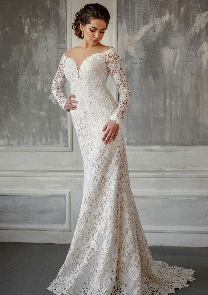 Ажурное свадебное платье облегающего кроя с глубоким декольте и сдержанным рукавом.