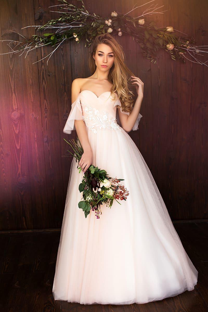 Кремовое свадебное платье с открытым лифом в форме сердца и многослойной юбкой.