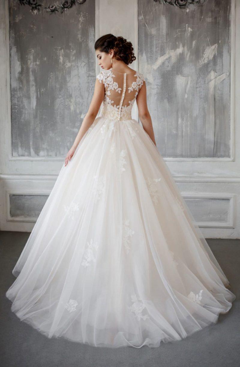 Пышное свадебное платье с прозрачной спинкой и романтичными аппликациями на юбке.