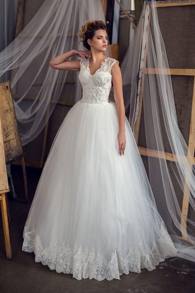 Пышное свадебное платье с фактурным кружевом на лифе и смелым вырезом на спине.
