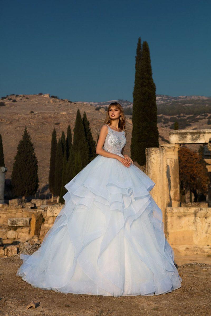 Очаровательное свадебное платье с полупрозрачным лифом и пышной юбкой сложного кроя.