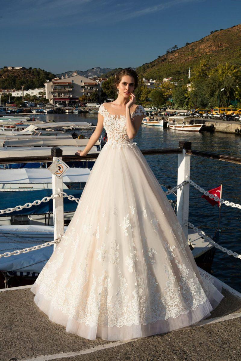 Бежевое свадебное платье с романтичным пышным силуэтом, подчеркнутым аппликациями.