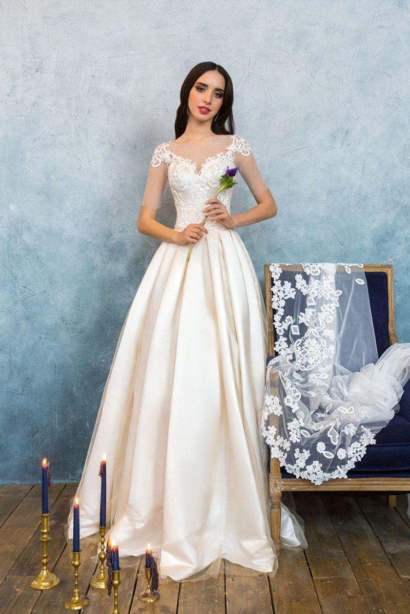 Кремовое свадебное платье с воздушной юбкой и корсетом, украшенным кружевом.