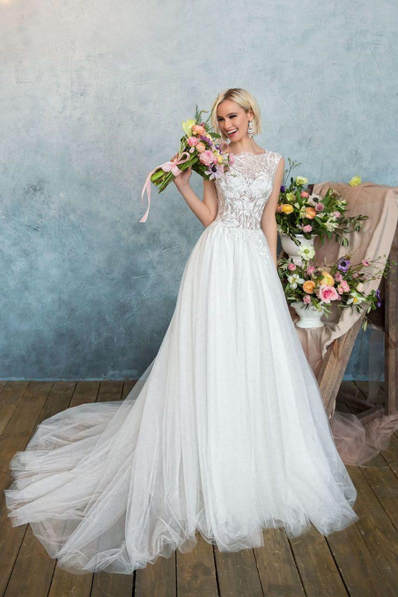 Очаровательное свадебное платье с многослойной юбкой и ажурным закрытым верхом.