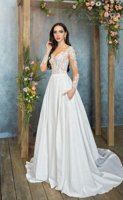 Свадебное платье изысканного А-силуэта с прозрачным рукавом с кружевной отделкой.