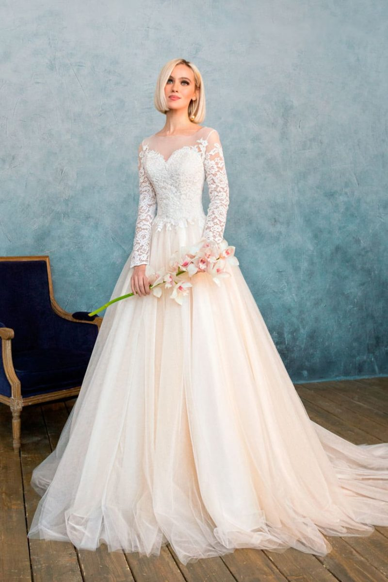 Закрытое свадебное платье с длинным кружевным рукавом и пышной кремовой юбкой.