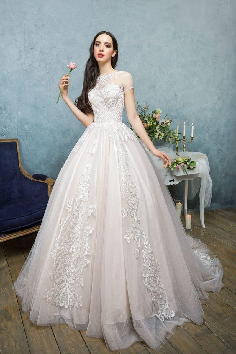 Пышное свадебное платье цвета слоновой кости, украшенное элегантной вышивкой.