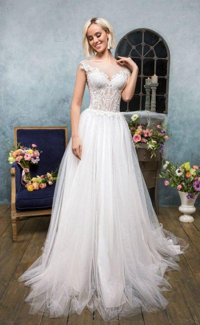 Свадебное платье с многослойной юбкой и полупрозрачным закрытым верхом из кружева.