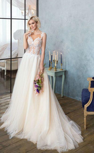 Кремовое свадебное платье с лифом с иллюзией прозрачности и многослойной юбкой.