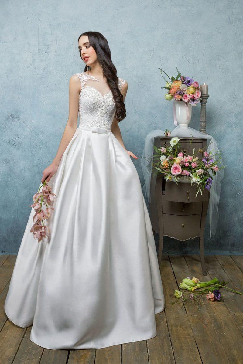 Пышное свадебное платье с ажурной вышивкой по закрытому лифу и юбкой из атласа.