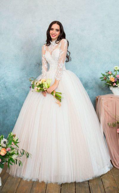 Закрытое свадебное платье с кремовой пышной юбкой и длинным ажурным рукавом.