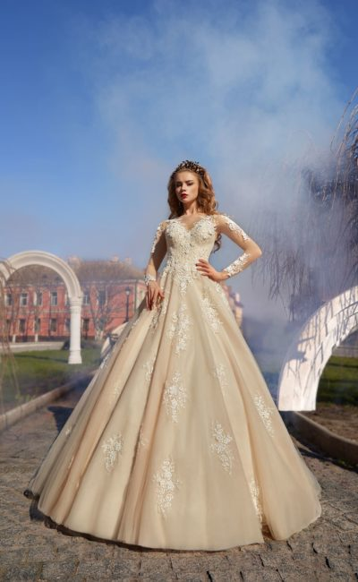Бежевое свадебное платье с объемной юбкой «принцесса» и полупрозрачными рукавами.