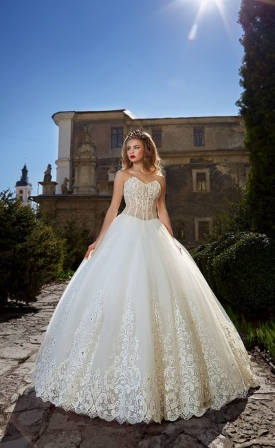 Открытое свадебное платье с полупрозрачным корсетом и пышной юбкой с кружевным низом.