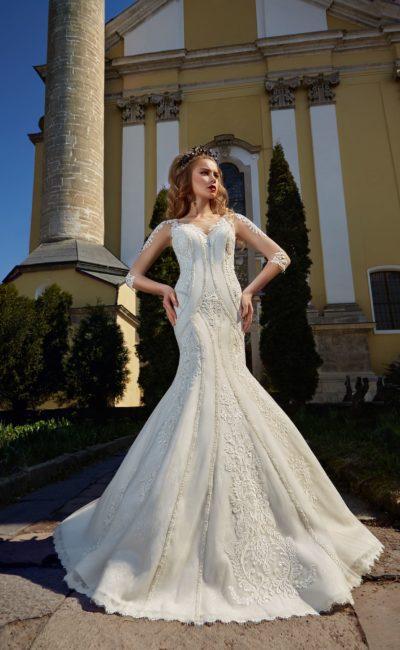 Облегающее свадебное платье с длинным рукавом и нежными кружевными аппликациями.