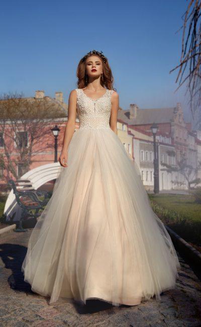Романтичное свадебное платье с многослойной бежевой юбкой и стильным декором лифа.