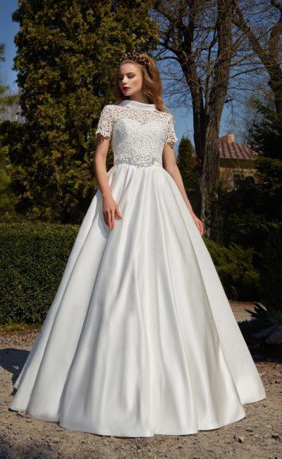 Атласное свадебное платье с юбкой А-силуэта и закрытым кружевным верхом с коротким рукавом.