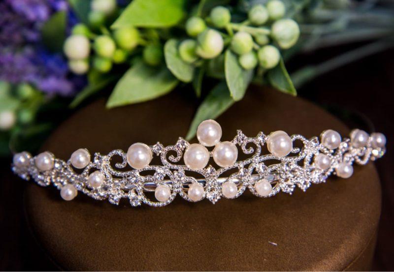 Нежная свадебная корона, покрытая маленькими стразами и крупными жемчужинами.
