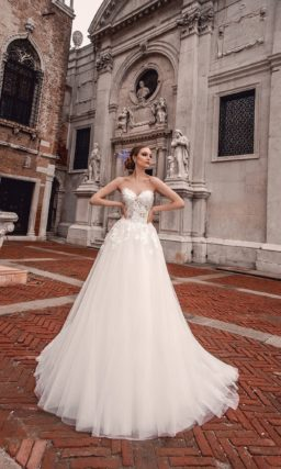 Романтичное свадебное платье с открытым кружевным корсетом и многослойной юбкой.