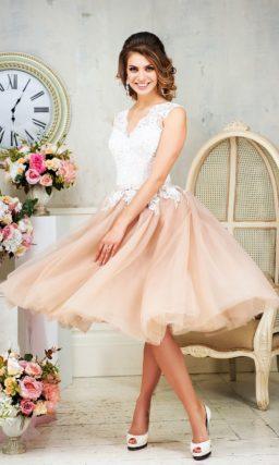 Короткое свадебное платье с кремовой юбкой и белым верхом, оформленным кружевом.