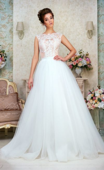 Царственное свадебное платье с воздушным подолом и кремовым верхом с вырезом сзади.