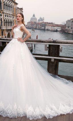 Великолепное свадебное платье с открытым лифом и роскошной пышной юбкой со шлейфом.
