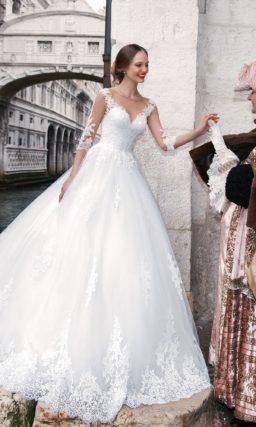 Классическое свадебное платье пышного кроя с длинным рукавом из кружевной ткани.