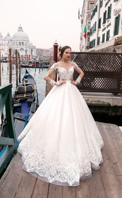 Пышное свадебное платье с кружевным лифом на бежевой подкладке и длинным рукавом.