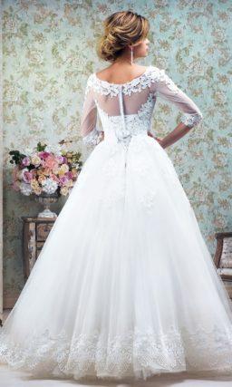 Пышное свадебное платье с полупрозрачными рукавами и отделкой аппликациями.