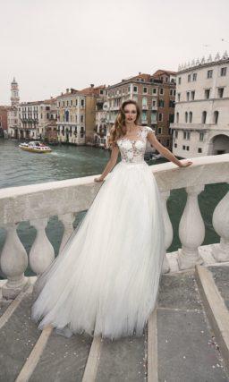 Романтичное свадебное платье с воздушной юбкой и лифом, покрытым крупным кружевом.