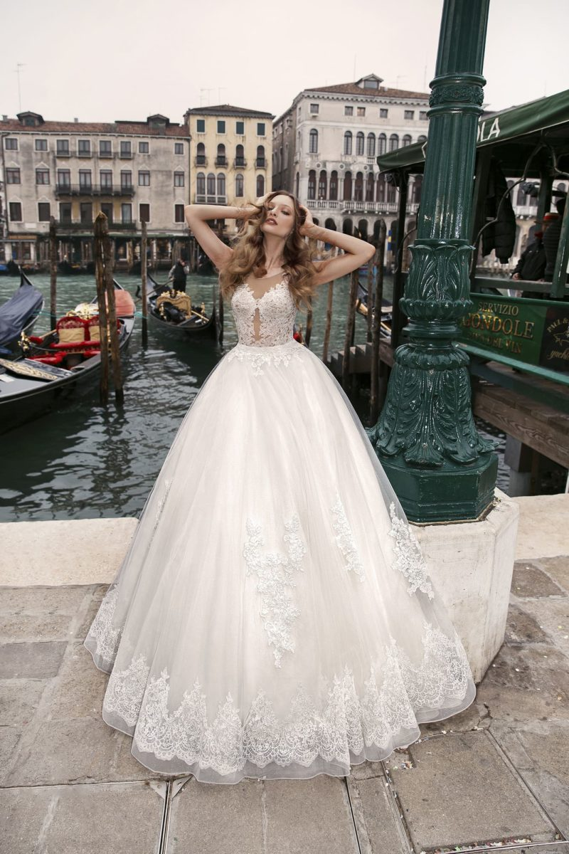 Кружевное свадебное платье с пышной юбкой и эффектным декольте на тонком лифе.